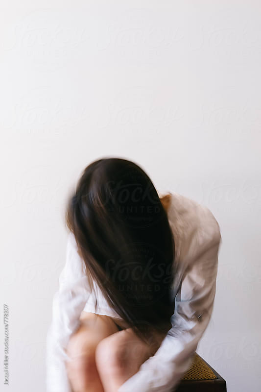 Unrecognisable woman leaning forward, hugging her knees, intentional movement and blur by Jacqui Miller for Stocksy United