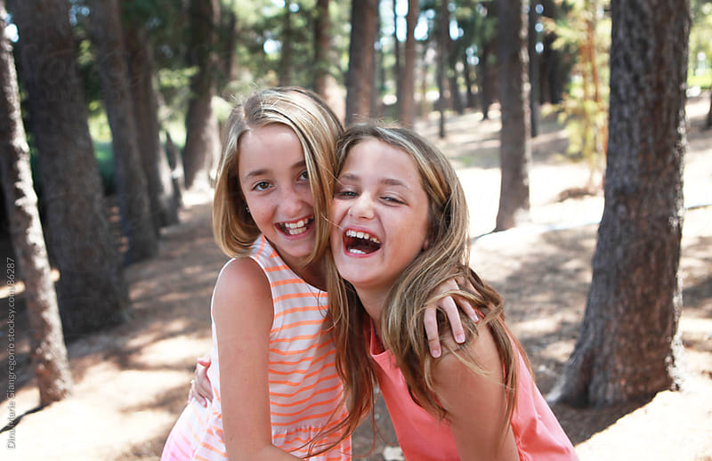 Two young girls laughing in park by Dina Giangregorio for Stocksy United