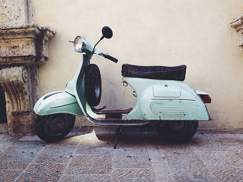 A motor scooter stands against a wall in an old Italian village by Greg Schmigel for Stocksy United