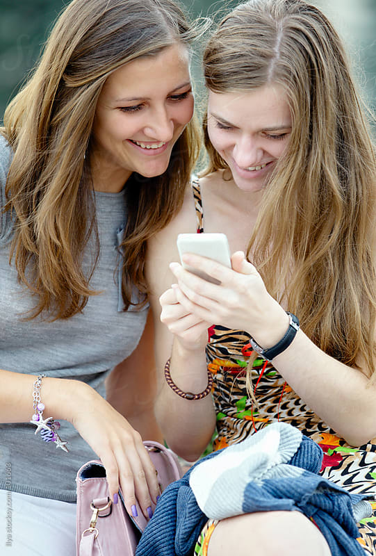 Two young happy women friendly chatting outdoors looking at mobile phone. by Ilya for Stocksy United