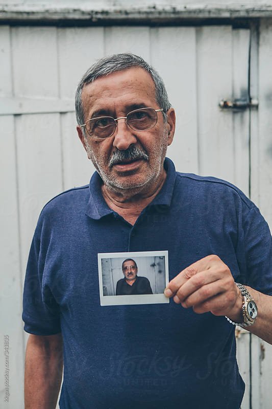Senior man holding a polaroid portrait of himself by kkgas for Stocksy United