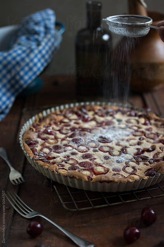 Cherry clafoutis: Sprinkled with icing sugar. by Darren Muir for Stocksy United