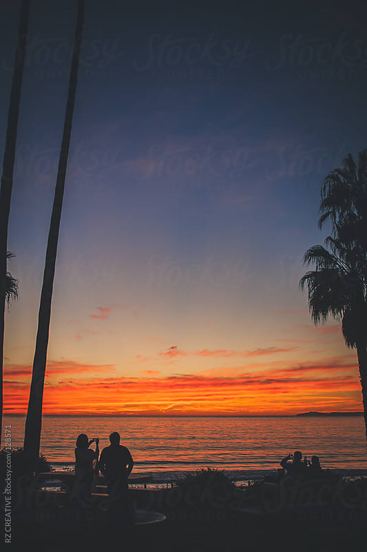 Two couples enjoy a vibrant fall sunset. by RZ CREATIVE for Stocksy United