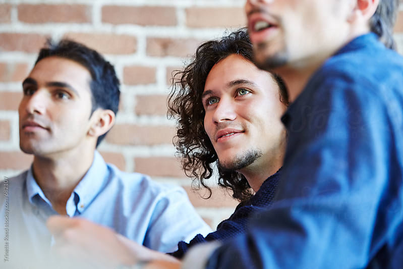 Close-up portrait of three millennial businessmen in meeting by Trinette Reed for Stocksy United