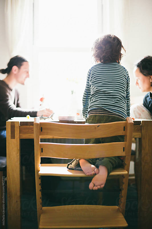 Family sitting around the table by michela ravasio for Stocksy United