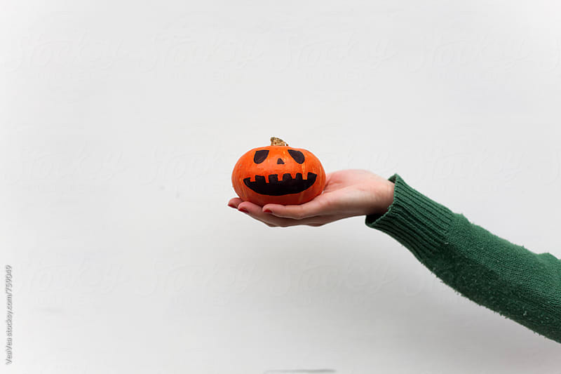 Female hand holding a small Halloween pumpkin on a white wall  by Marija Mandic for Stocksy United
