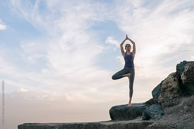 Young woman in tree pose on waterfront rocks by T-REX & Flower for Stocksy United