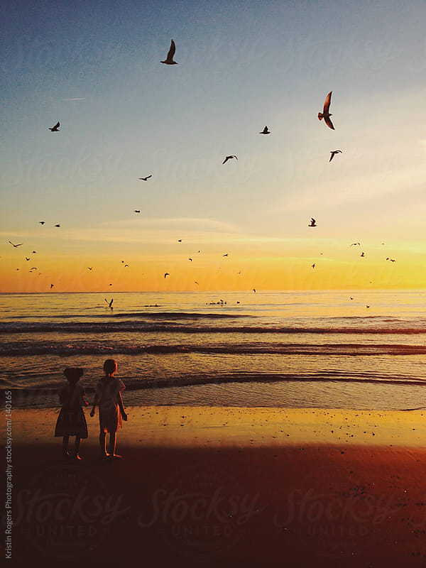 Sisters looking in awe of birds flying all over the beach at sunset by Kristin Rogers Photography for Stocksy United