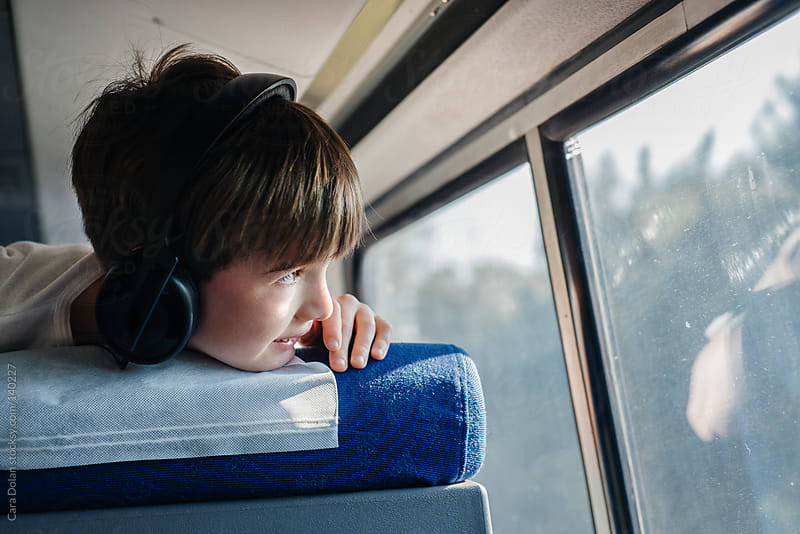 Boy with headphones watches out the window of a train by Cara Dolan for Stocksy United