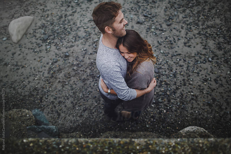 Young happy couple hugging each other outside with affection by Rob and Julia Campbell for Stocksy United