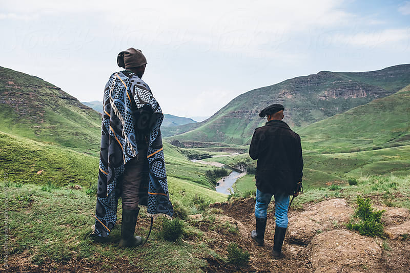 Basotho herdsmen standing on a hill top overlooking a mountainous valley in Lesotho by Micky Wiswedel for Stocksy United