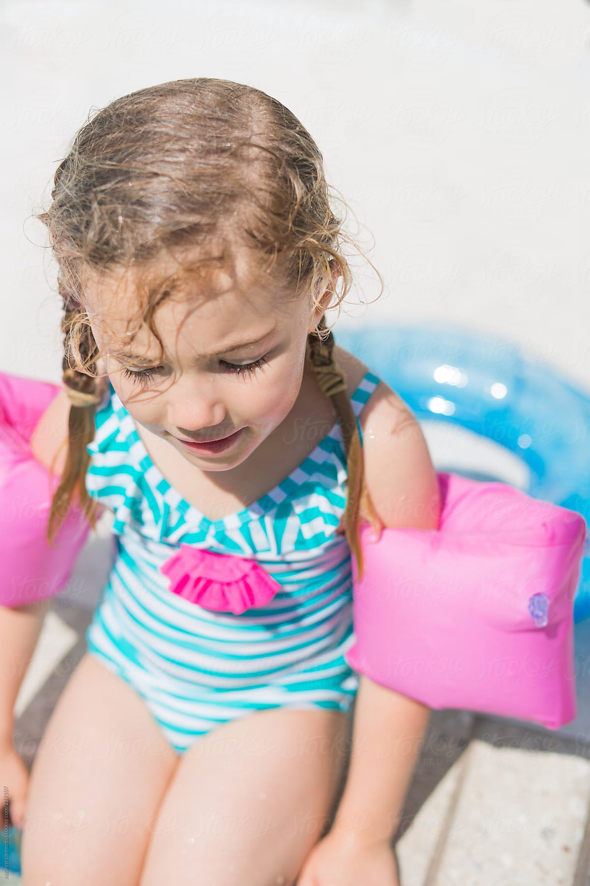 3b1053fd582 Little Girl in Her Swimsuit and Swimmies at the Pool by suzanne clements  for Stocksy United