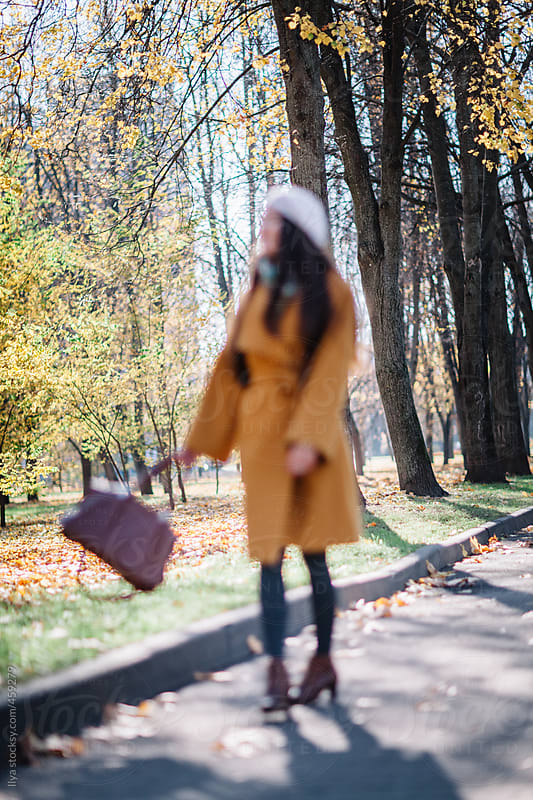 Young defocused anonymous woman walking on the street (blurred by lens) by Ilya for Stocksy United
