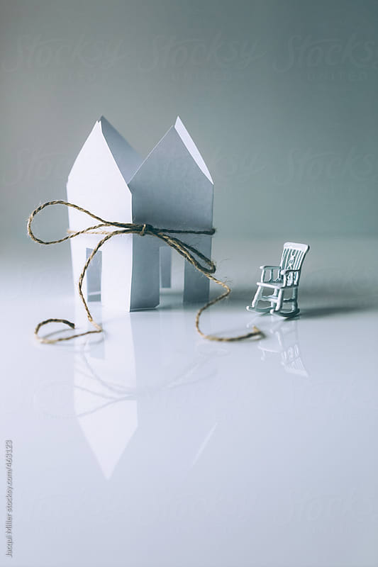 Small white rocking chair next to white paper houses tied up with string by Jacqui Miller for Stocksy United