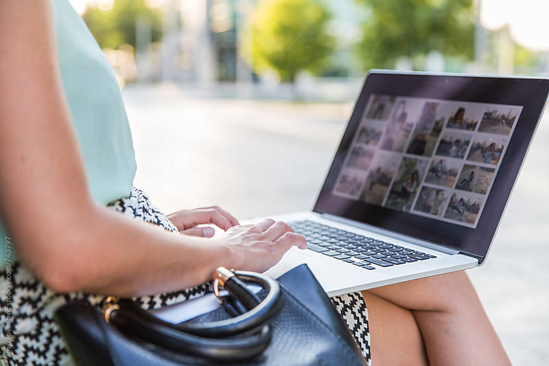 Woman working on a laptop outdoors by Jovo Jovanovic for Stocksy United