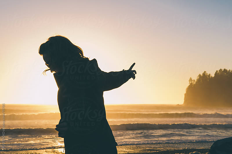 Carefree happy woman at sunset beach with haystack rocks by TRU STUDIO for Stocksy United