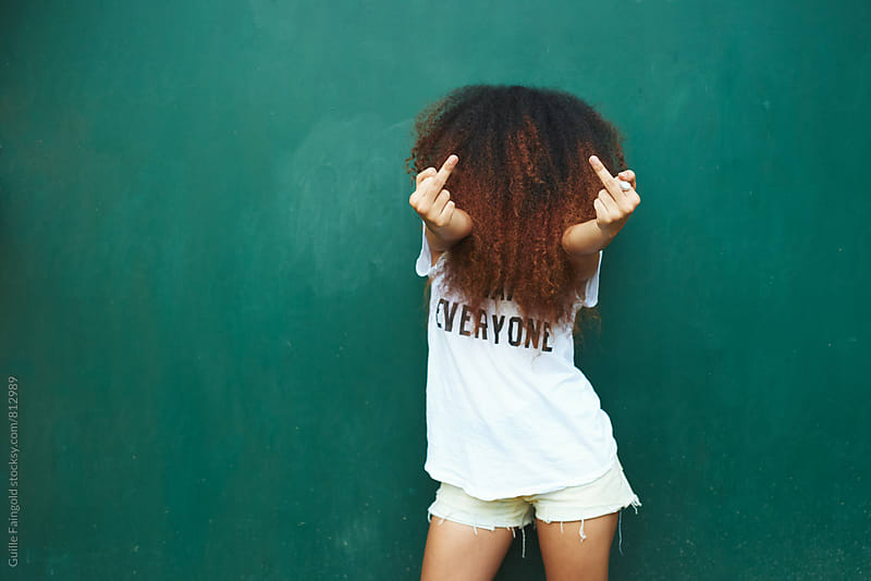 Young woman with face covered in curly hair showing middle fingers by Guille Faingold for Stocksy United