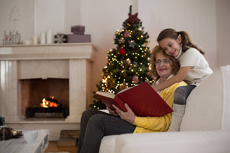 Grandmother and Granddaughter Reading a Book at Christmas by Lumina for Stocksy United