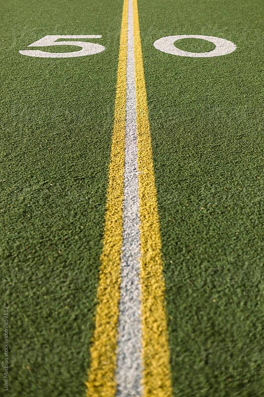 Fifty Yard Line Marked On Turf Football Field by Luke Mattson for Stocksy United