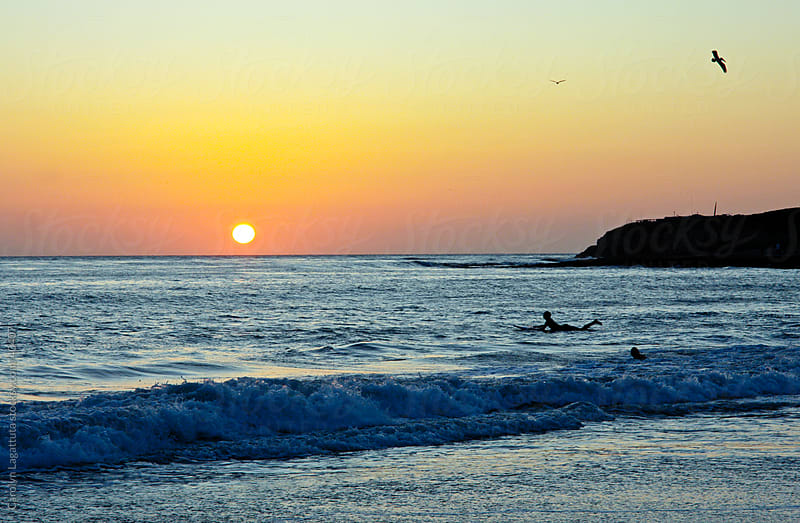 A surfer paddling out at sunset in Santa Cruz by Carolyn Lagattuta for Stocksy United