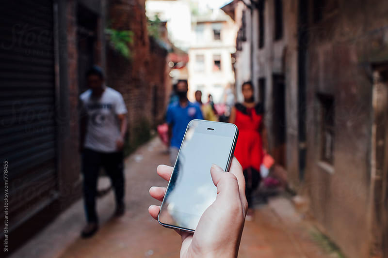 Hand of a woman using a mobile app to navigate in the streets of Asia. by Shikhar Bhattarai for Stocksy United