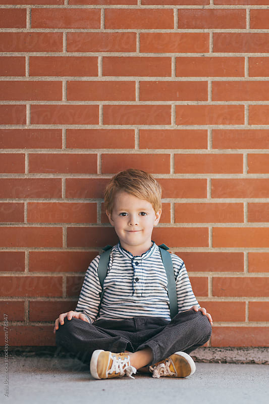A blonde boy sitting against a brick wall with his legs crossed by Ania Boniecka for Stocksy United
