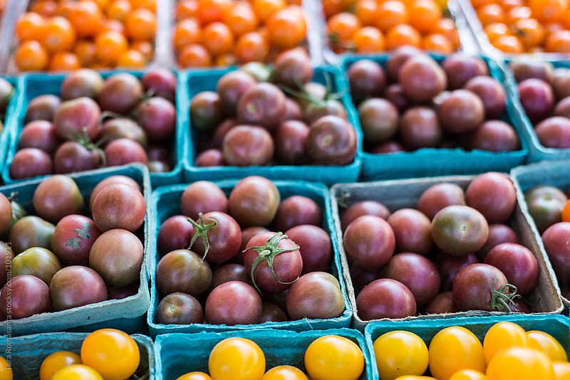 cartons of colorful tomatoes at the farmers market by Tara Romasanta for Stocksy United