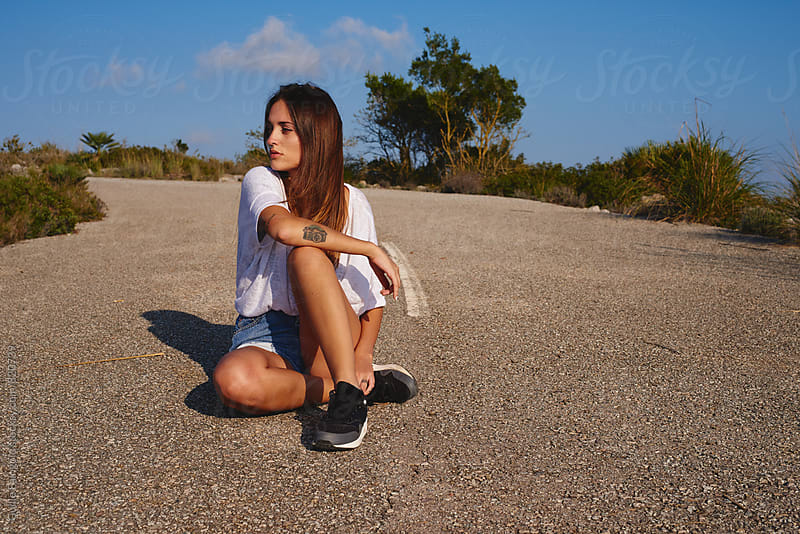 Young woman sitting on road and looking away by Guille Faingold for Stocksy United