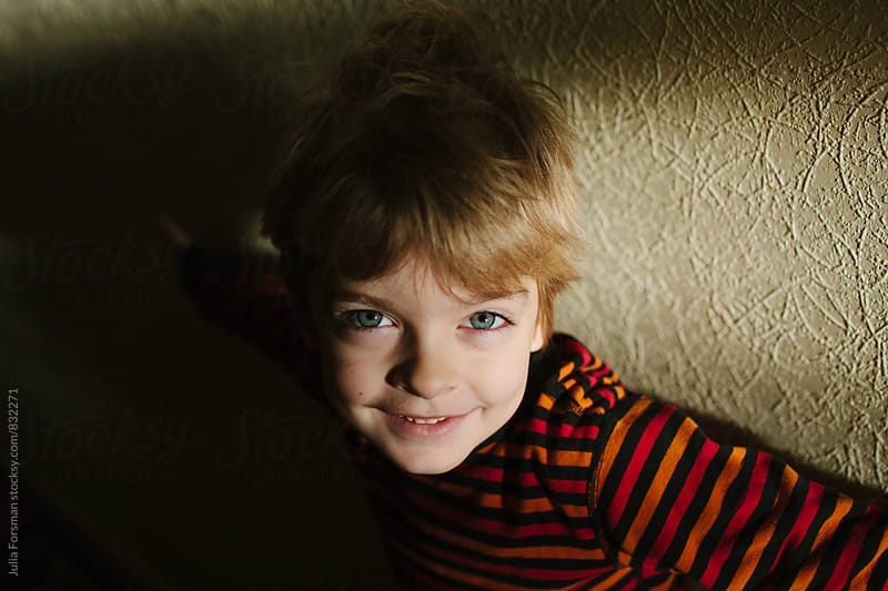 Young boy smiling in strong light and shadow. by Julia Forsman for Stocksy United
