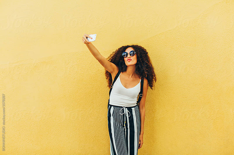 Portrait of a chic tourist taking a selfie in front of a yellow wall.  by BONNINSTUDIO for Stocksy United