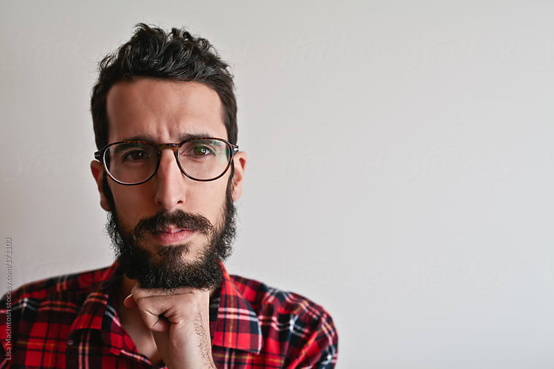 handsome, bearded young man with glasses and plaid shirt, resting chin on fist by Lisa MacIntosh for Stocksy United