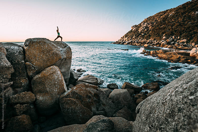 Young fit woman doing yoga on a rocky beach at sunset by Micky Wiswedel for Stocksy United