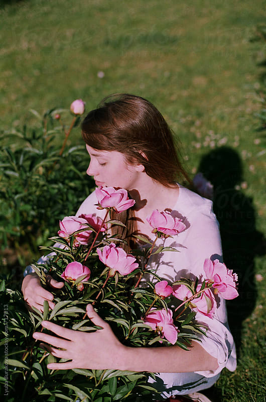 Young woman hugs a bunch of peonies  by Lyuba Burakova for Stocksy United