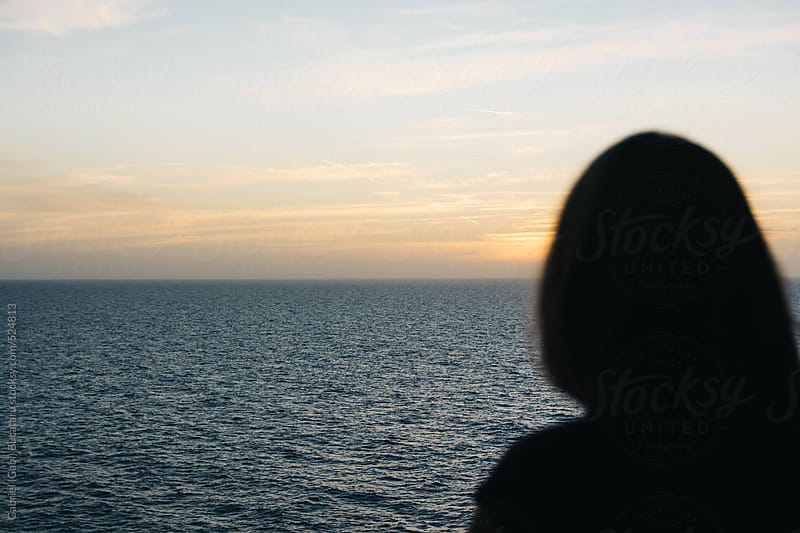 Silhouette of a woman looking at an ocean sunset by Gabriel (Gabi) Bucataru for Stocksy United