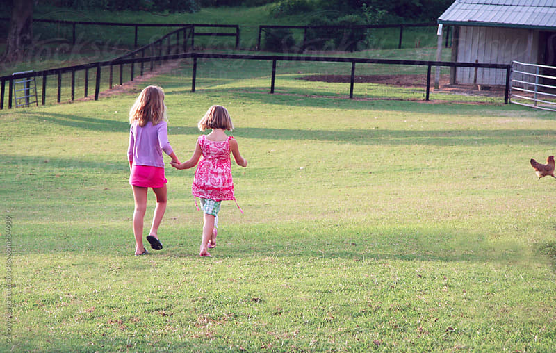 Cousins holding hands and waking toward the barn by Carolyn Lagattuta for Stocksy United