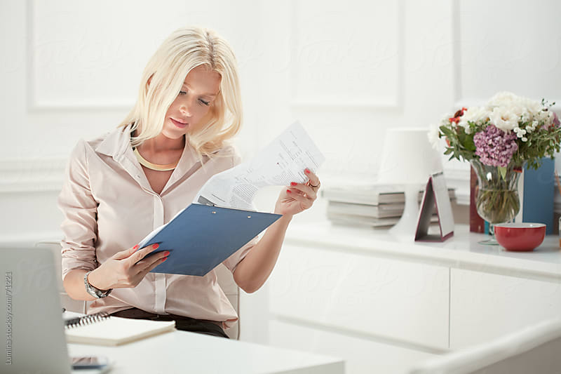 Businesswoman Reading Documents  by Lumina for Stocksy United
