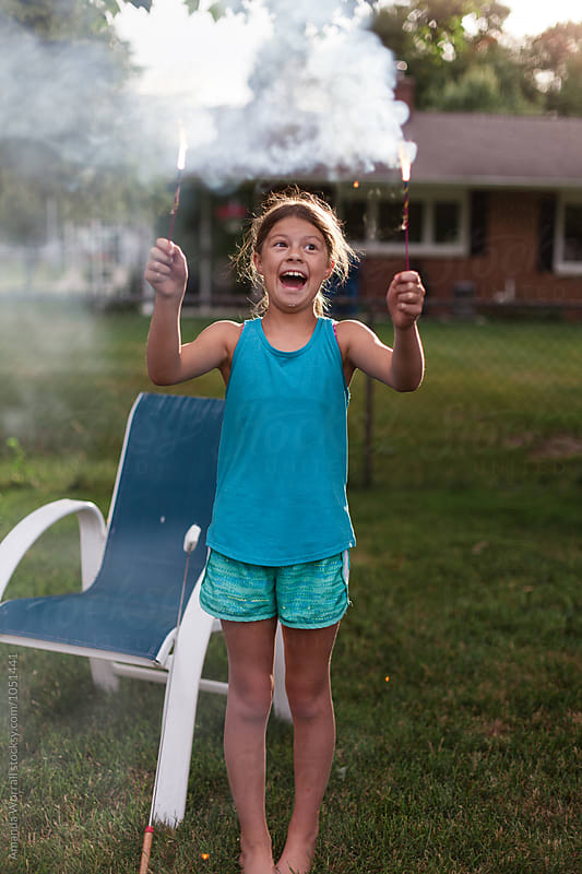 Smiling tween girl holding sparklers in backyard by Amanda Worrall for Stocksy United