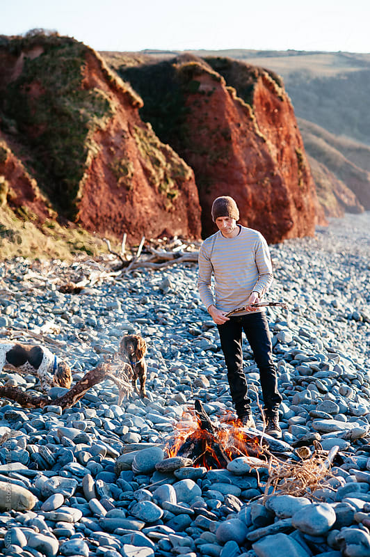Man standing next to a fire on a beach with his dogs by Suzi Marshall for Stocksy United