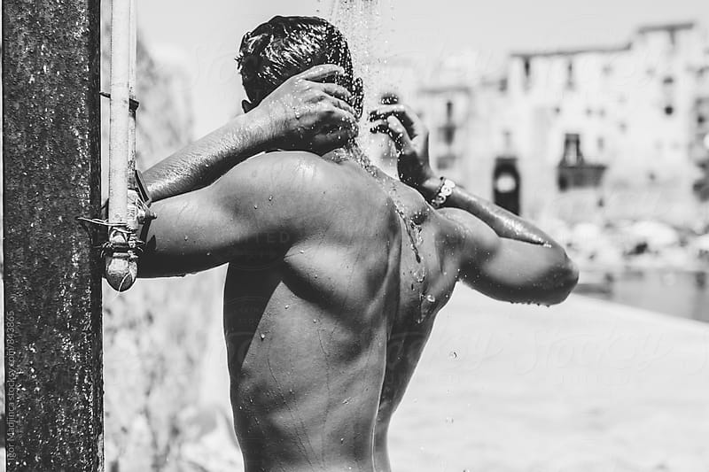 happy handsome young man taking a shower at the beach, Sicily by Igor Madjinca for Stocksy United