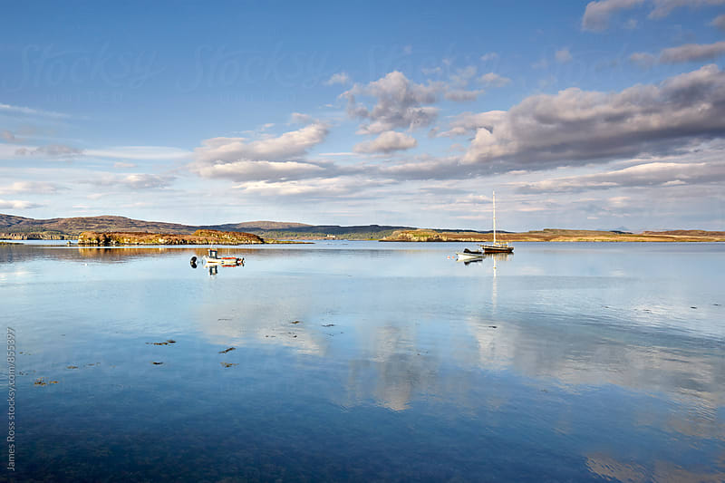 Moored boats on a loch, Scotland by James Ross for Stocksy United