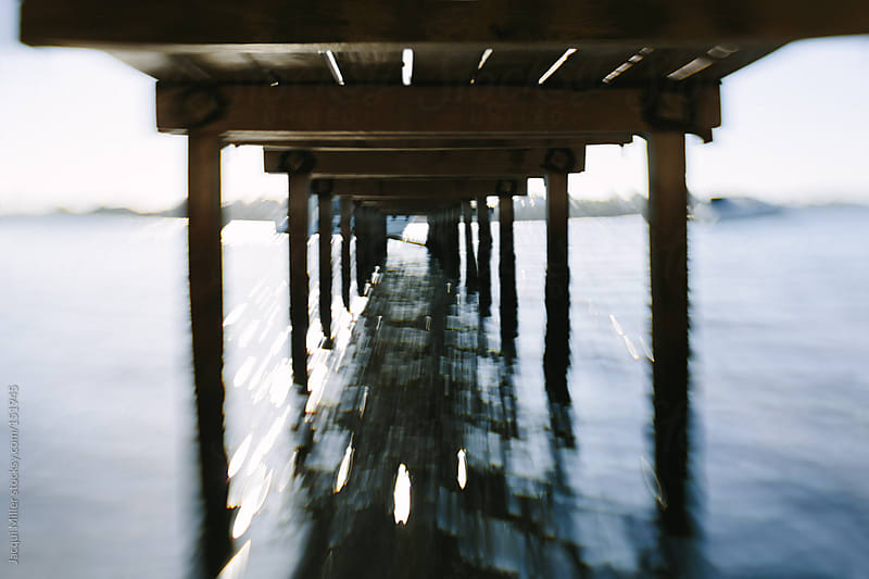 View of the underside of a jetty in the morning.  by Jacqui Miller for Stocksy United