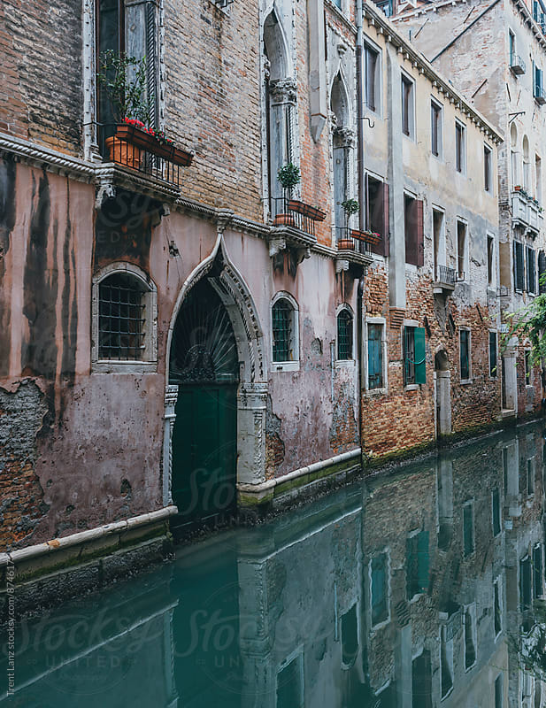Reflection view on Venice canal between old buildings at daytime by Trent Lanz for Stocksy United