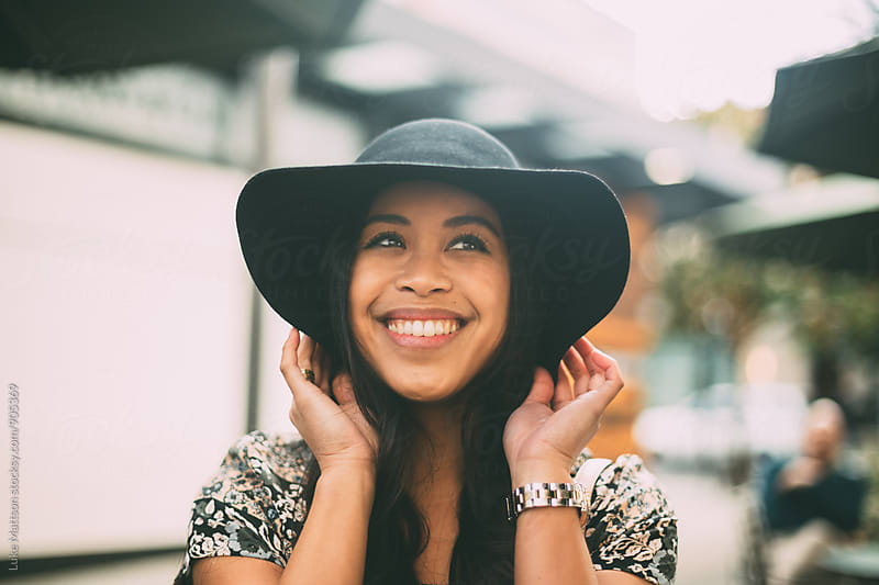 Smiling Young Woman Holding Brim Of Sun Hat With Two Hands by Luke Mattson for Stocksy United