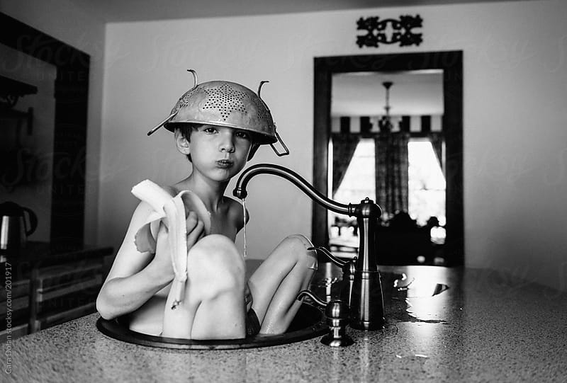 Boy with strainer on his head soaks in the kitchen sink by Cara Dolan for Stocksy United