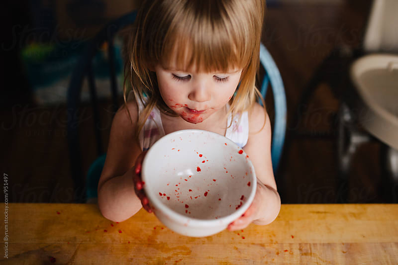 Toddler girl holding bowl after eating red jello by Jessica Byrum for Stocksy United