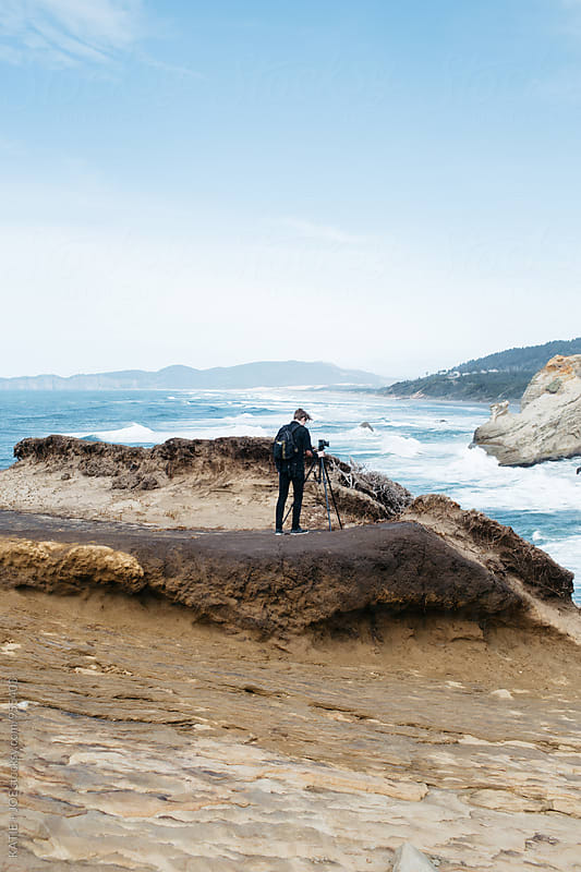 Man standing on the edge of a rock overlooking the ocean with a tripod  by KATIE + JOE for Stocksy United