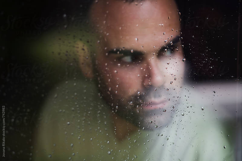 Portrait of a man standing at the window watching the rain by Jovana Rikalo for Stocksy United