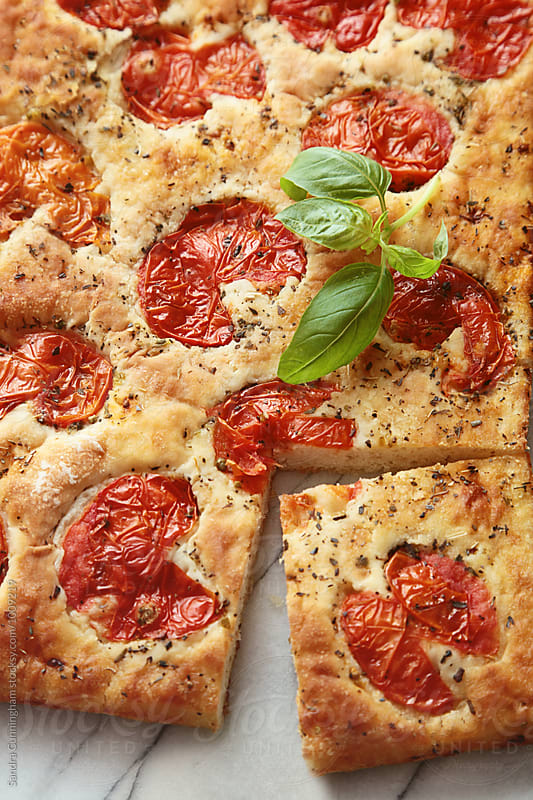Closeup of focaccia bread with tomatoes and basil by Sandra Cunningham for Stocksy United