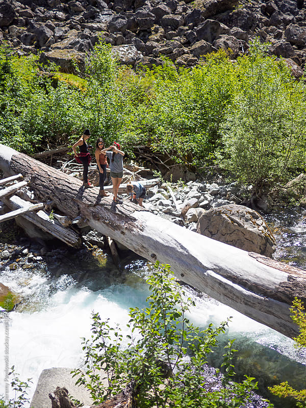 Four young woman hiking near log, rocks and river in Washington, USA by Jeremy Pawlowski for Stocksy United