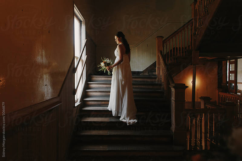Bride Standing by Window on Stairs by Sidney Morgan for Stocksy United